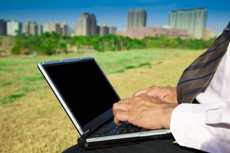 Business man working on a laptop outdoors sitting on a park bench Stock Photo - 6791217