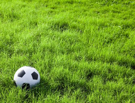Soccer ball or football on the grass field photo