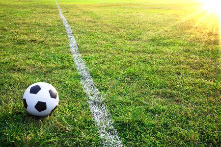lejos: un bal�n de f�tbol o f�tbol en el estadio con la puesta de sol