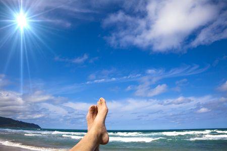 Liggend op het strand genieten van de zon Stockfoto