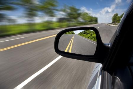 conducci�n: coche a trav�s de la carretera vac�a y el enfoque en el espejo