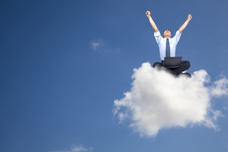young businessman with computer sitting on the cloud photo