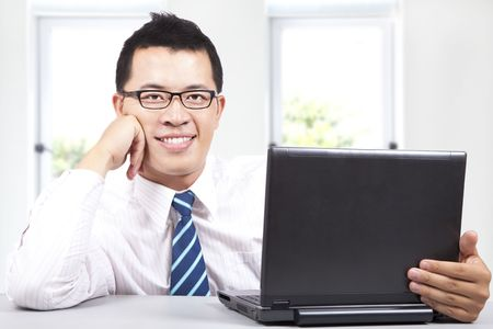 laptop asian: trabajo de empresario de �xito joven sonriente con equipo  Foto de archivo