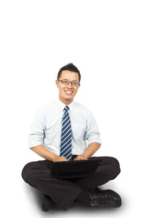 floor standing: smiling young businessman sitting and using laptop isolated on white background
