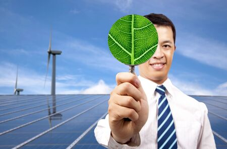 green energy business concept.young businessman holding Magnifier and standing in front of solar panel and wind turbine Stock Photo - 7621576