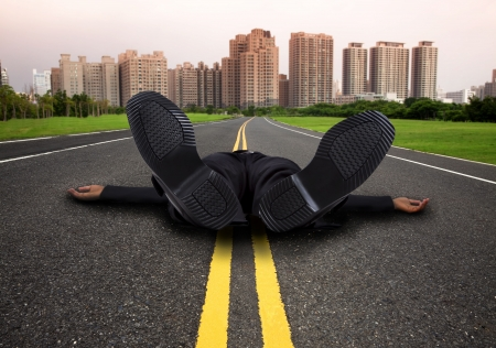 businessman tired and Exhausted on the empty  road to the city photo