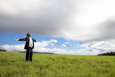 spring break: happy and Relaxation businessman standing on the green field enjoy sunlight