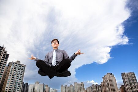 self confidence: Businessman meditating in the air before modern building