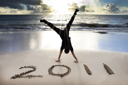 happy new year 2011 on the beach of sunrise . young man handstand and celebrate . photo
