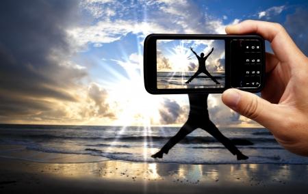 hands free phone: Tel�fono m�vil con c�mara y hombre salto feliz en la playa de hermoso amanecer