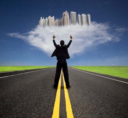 businessman standing on the empty road and watching the future city on the cloud photo