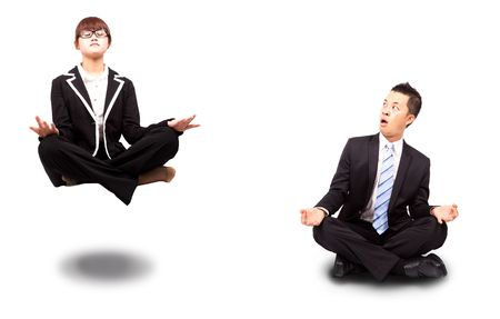businesswoman and businessman in yoga lotus-pose and relaxing. Surprised man watching woman Floating in the air photo