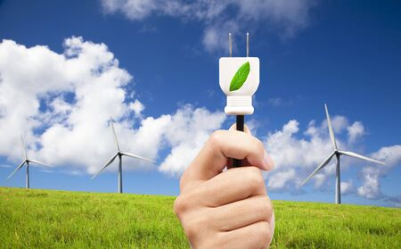 hand hold eco power plug and Wind turbines on blue sky  photo