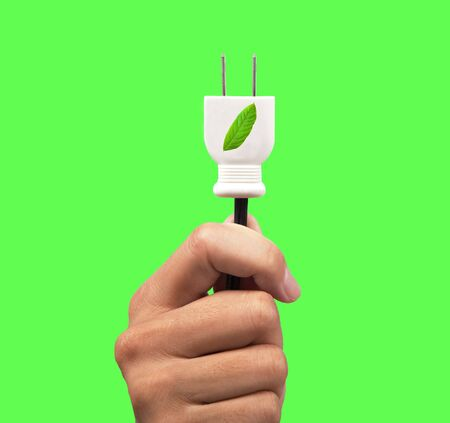 hand holding eco power plug and leaf logo with green background photo