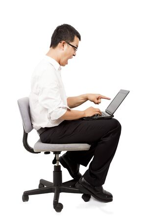 Angry businessman screaming against a laptop on the chair photo