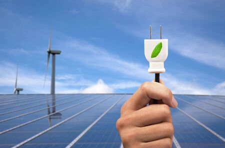 eco power concept.hand holding green power plug and solar panel and wind turbine background Stock Photo - 7899923