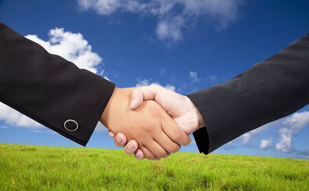 Close-up of a business people shaking hands against blue sky and green background  photo