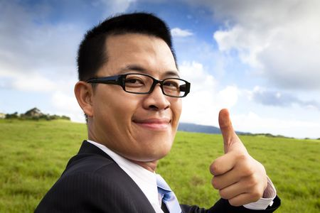 young smiling and confident businessman with thumb up photo