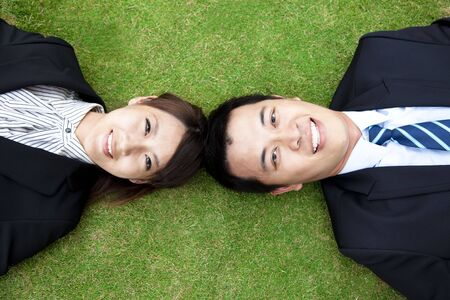 friendly competition: business couple.happy  businessman and woman Lay on the grass Stock Photo