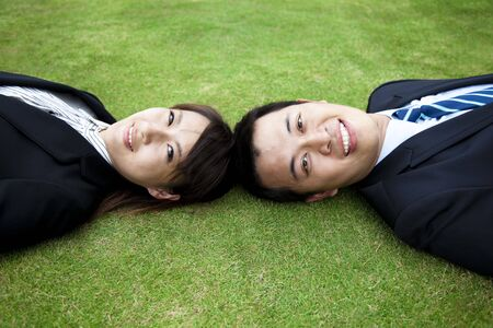 Attractive young adult couple and lay on the grass field Stock Photo - 8127146