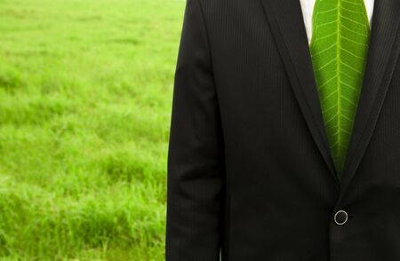 Businessman with green leaf tie on the grass field photo