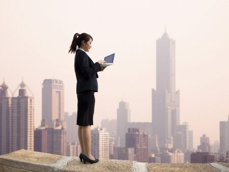 Businesswoman using computer and  stand on the top of a skyscraper with cityscape  photo