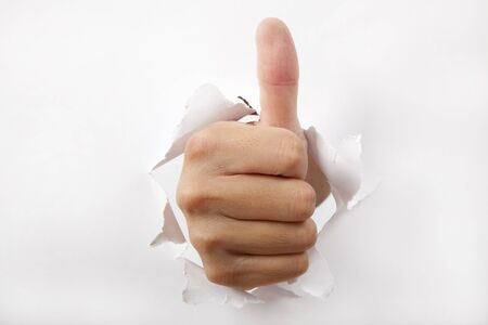 commend: hand break through the white paper with Thumb up