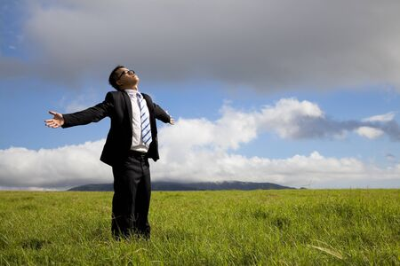 human mind: Relaxation businessman standing on the meadow