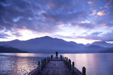 mood moody: Man stand on a pier and watching the mountains and lake Stock Photo