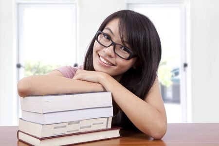 Beautiful smiling girl in a classroom with book photo