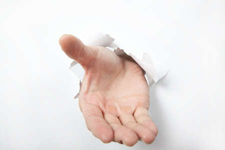 Hand punching through white  paper and try to shake or take some one  photo