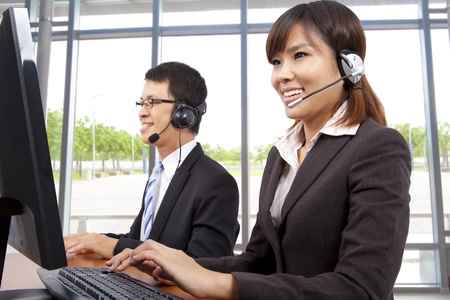 representative: Smiling customer service representative in modern office with a headset