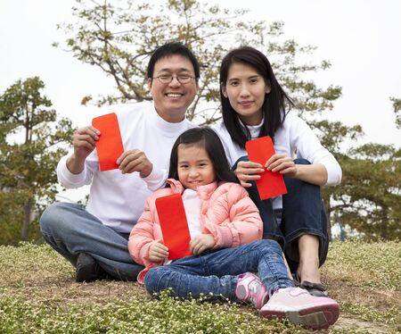 Happy chinese family holding red envelop celebrating chinese new year photo