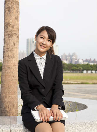 Smiling and beautiful asian businesswoman holding laptop and sitting in the city park Stock Photo - 8564548