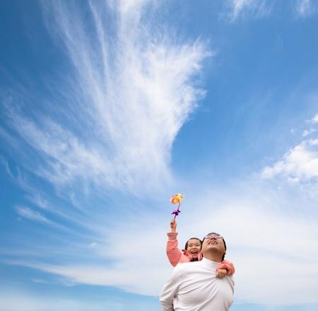 Niña feliz y padre con fondo de nubes y el cielo Foto de archivo - 8595610