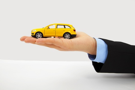 car insurance: Businessmans hand holding a car