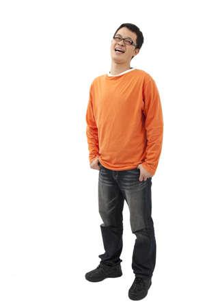 young man standing: Asian giovane uomo in piedi con le mani nelle tasche isolati su sfondo bianco