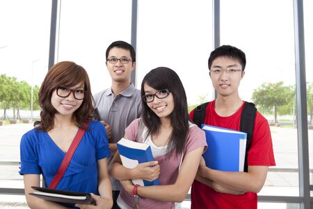 Young smiling students stand in the classroom