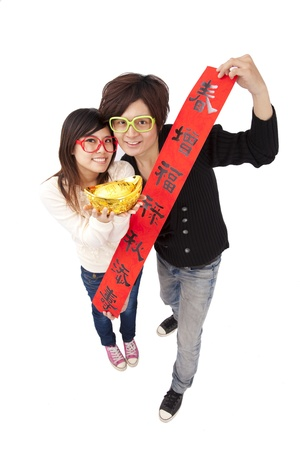 Happy chinese new year. Young couple holding gold ingot and red spring couplets photo