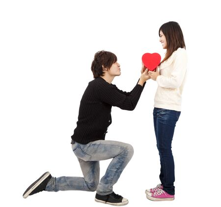 the lovely boy: Asian young Man handing over love gift  to  young woman on Valentine Day isolated on white background  Stock Photo