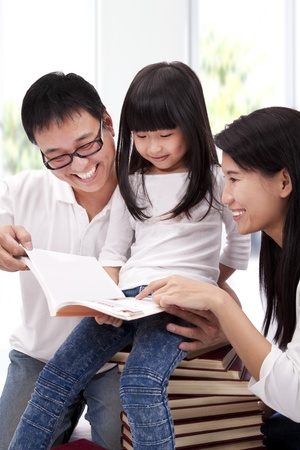 happy asian family: Happy asian family studiyng together. Parent helping daughter  reading book