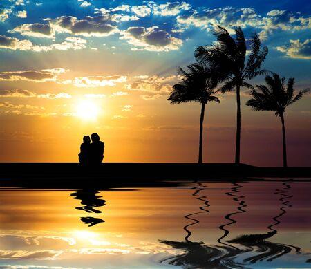 luna de miel: La silueta de la pareja viendo la puesta de sol en la playa Foto de archivo