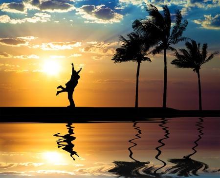 femme romantique: Magnifique coucher de soleil sur la plage et la silhouette du couple heureux Banque d'images