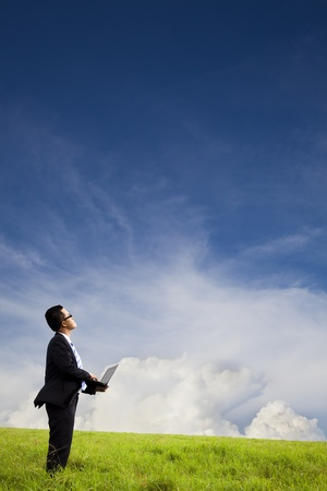 working environment: Businessman holding computer and watching the cloud