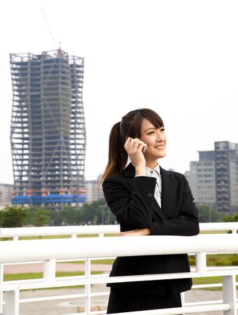 Happy asian business woman talking on the phone and office building background photo