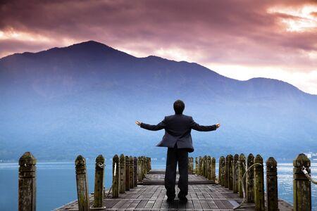 vision futuro: Soporte de empresario en el muelle y viendo la monta�a y la nube de sunrise