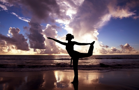 Yoga woman on the beautiful beach at sunrise photo