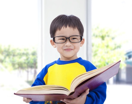 kid sitting: Asian kid smiling and holding book Stock Photo
