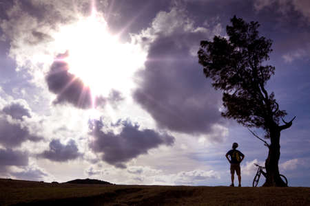 amaze: Bicycle rider stand on the hill watching the sunlight and  relax  Stock Photo