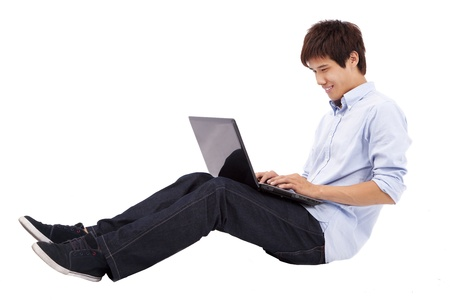 Happy and relax young man using laptop on the floor isolated on white background Stock Photo - 9075988